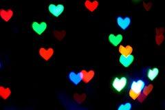 Multi покрашенные запачканные света в форме сердец в темноте стоковые фото
