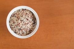 Multi покрашенный рис на белом шаре. Деревянная предпосылка Стоковые Изображения RF