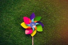 Multi покрашенный pinwheel на предпосылке зеленого стекла весны, над v Стоковые Изображения RF
