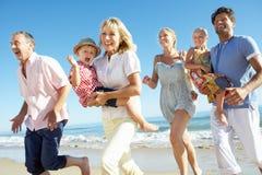 Multi семья поколения наслаждаясь праздником пляжа Стоковые Фото