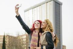 Multi этнические друзья имея потеху в городе принимая selfie Стоковое Изображение