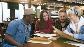 4 multi этнических друз выбирая блюда от меню в баре, паба акции видеоматериалы