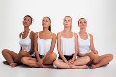4 multi этнических женщины сидя на поле Стоковое Изображение RF