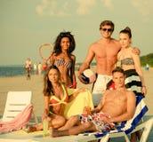 Multi amici etnici una spiaggia Immagine Stock