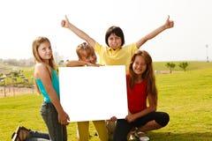 Multi bambini etnici sorridenti con un tabellone per le affissioni Fotografia Stock Libera da Diritti