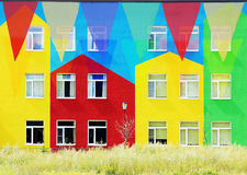 Multi bandeiras triangulares coloridas que penduram contra o contexto de casas coloridas Fotos de Stock Royalty Free