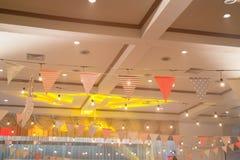 Multi bandiere colorate del triangolo che appendono partito dell'interno Immagine Stock