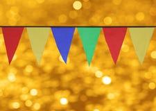 Multi bandiere triangolari colorate che appendono contro il contesto del bokeh dell'oro Immagine Stock