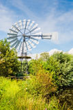 Multi-bladed wind pump between the shrubs Stock Photos