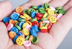 Multi botões coloridos em sua mão Imagens de Stock Royalty Free