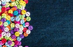 Multi botões coloridos em uma sarja de Nimes Imagens de Stock Royalty Free