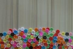 Multi botões coloridos na tabela de madeira clara Foto de Stock Royalty Free