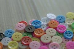 Multi botões coloridos na tabela de madeira clara Fotografia de Stock Royalty Free