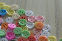 Multi botões coloridos na tabela de madeira clara Fotografia de Stock