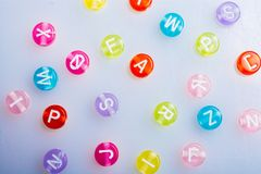 Multi color alphabet letter beads placed randomly royalty free stock photos