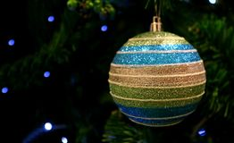 Multi Color Ball Shaped Glitter Ornament Hanging on the Sparkling Christmas Tree stock image