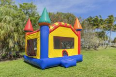 A multi-color castle bounce house photographed from the left side. The inflated bounce house has pops of color everywhere sits at the park on a beautiful sunny royalty free stock photos