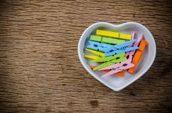 clothespins in heart shape bowl , valentine concept stock image