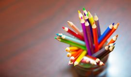 Color pencil in a clear jar. Multi-color Color pencil in a jar sitting on an empty table Stock Image