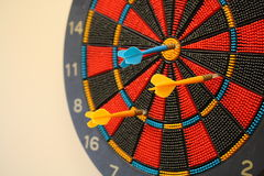 Multi color dart board with darts stuck in it Stock Photos