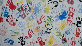 Colorful hand prints on the wall. Multi color hand prints painted over a white wall of a hostel royalty free stock photo