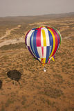 Multi color hot air balloon. Verticle image of a multi color hot air balloon flying above the desert Royalty Free Stock Image