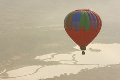 Multi color hot air balloon in flight. Over a hazy lake Stock Photography