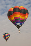 Multi color hot air balloons flying in blue sky. Verticle image of two multi color hot air balloons flying in a clear blue sky Stock Photo