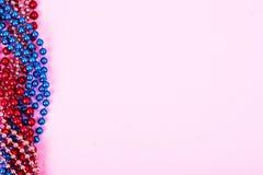Multi color Mardi Gras beads on bright background. Studi Photo stock photo