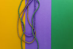 Multi color Mardi Gras beads on paper background. Top view stock photos
