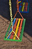 Multi-color painted swing for child on playground Royalty Free Stock Photography