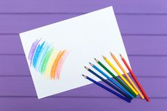 Multi-color pencil with blank white paper. Multi-color pencils with painted rainbow on white paper on purple wooden background Royalty Free Stock Photos