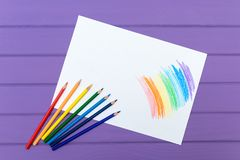 Multi-color pencil with blank white paper. Multi-color pencils with painted rainbow on white paper on purple wooden background Stock Image