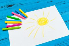 Multi-color pencil with blank white paper. The side view of multi-color pencils with painted sun on white paper on blue wooden background Stock Image