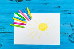 Multi-color pencil with blank white paper. The top view of multi-color pencils with painted sun on white paper on blue wooden background Royalty Free Stock Images