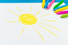 Multi-color pencil with blank white paper. The top view of multi-color pencils with painted sun on white paper on blue wooden background Stock Photo