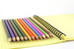 Multi color pencils. Color pencils on the yellow writing-book. Shallow DOF Royalty Free Stock Photos