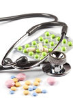 Multi color pills spills around the stethoscope Royalty Free Stock Photo