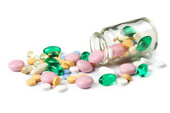 Multi color pills spills out of the little jar Royalty Free Stock Images