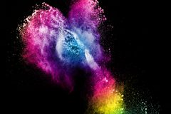Multi color powder explosion isolated on black background. Colorful dust splatter on dark background stock photo