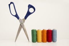 Multi color Sewing Threads and Scissor. Multicolor Sewing Threads, Bobbins Beside Open Leged Blue Scissor Isolated on White Background Royalty Free Stock Photography