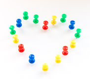 Multi color thumb-tacks arranged in heart shape. Stock Images