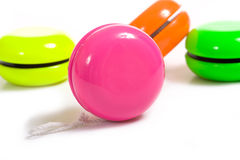 Multi-Color Yo-Yo's. A group of brightly colored Yo-Yo's on a white background.  Front pink Yo-Yo has copy space to add your own design or information Stock Images