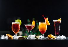 Multi-colored alcoholic cocktails with citrus in glasses of different shapes on the bar. stock photo