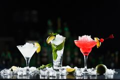Multi-colored alcoholic cocktails with citrus in glasses of different shapes on the bar. royalty free stock photo