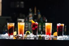 Multi-colored alcoholic cocktails with citrus in glasses of different shapes on the bar. stock photography