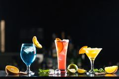 Multi-colored alcoholic cocktails with citrus in glasses of different shapes on the bar. stock photos