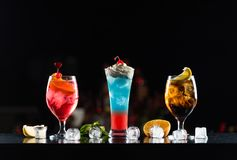 Multi-colored alcoholic cocktails in glasses of different shapes on the bar. royalty free stock photo