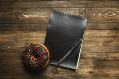 Multi-colored assortment of donuts. Chocolate donut with sprinkles and frosting on dark wooden background. with a notebook and pen Royalty Free Stock Photos