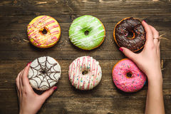Multi-colored assortment of donuts in hands. Multi-colored assortment of donuts with sprinkles and frosting on dark wooden background. six sweet rings in hands Royalty Free Stock Photos